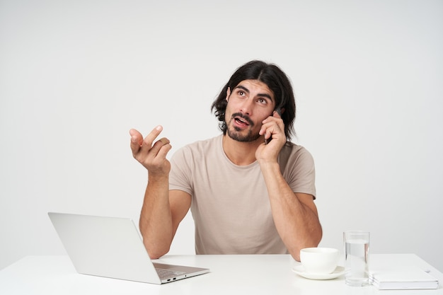 Portret van knappe, doordachte zakenman met zwart haar en baard. kantoor concept. praat aan de telefoon en maak gebaren. zittend op de werkplek, geïsoleerd over witte muur