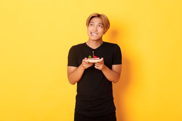 Portret van knappe dromerige aziatische kerel die linkerbovenhoek kijkt en denkt, wens doet terwijl hij verjaardag viert en verjaardagstaart vasthoudt, gele muur