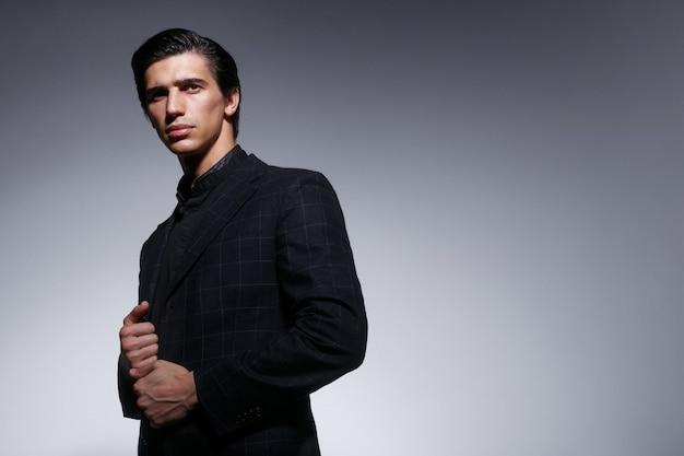 Portret van knappe elegante jongeman in stijlvol zwart pak, geïsoleerd op een grijze achtergrond. ruimte voor tekst.