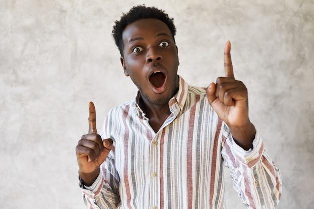 Portret van knappe emotionele jonge afrikaanse man verrast met grote verkoopprijzen, wijzende vingers omhoog, opgewonden,