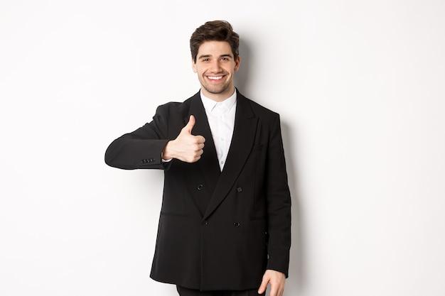 Portret van knappe en zelfverzekerde mannelijke makelaar, duim omhoog en glimlachen, kwaliteit garanderen en bedrijf aanbevelen, staande op een witte achtergrond