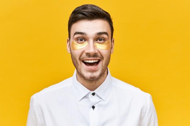 Portret van knappe energieke jonge mannelijke kantoormedewerker met opgewonden gezichtsuitdrukking die onder ooglapjes draagt om wallen, tekenen van vermoeidheid en stress te verminderen, zijn mond wijd openhoudend