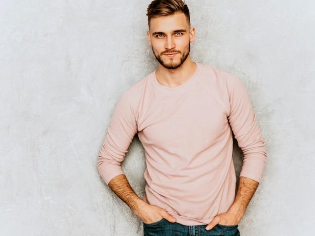 Portret van knappe ernstige jonge man model casual roze kleding dragen. mode stijlvolle man die zich voordeed