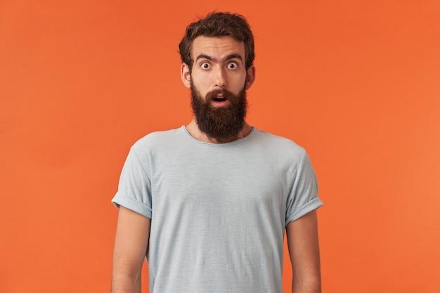 Portret van knappe europese of bebaarde jonge man met bruine ogen in wit t-shirt kijkt naar je emotie verrast verward en attent poseren staande