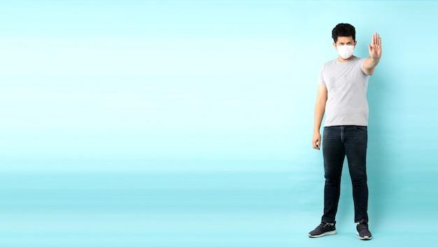 Portret van knappe full body aziatische man met een masker is ziek geïsoleerd op blauwe achtergrond in studio met kopie ruimte.