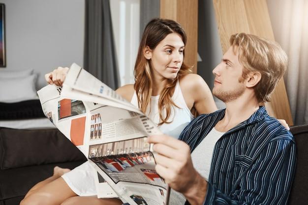 Portret van knappe gebaarde vriend die door meisje worden afgeleid terwijl thuis het lezen van krant. vrouw wil zijn aandacht trekken en vertelt hem iets verrassends.