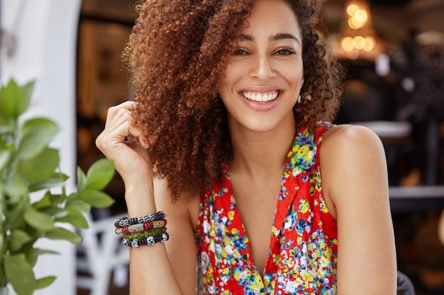 Portret van knappe gelukkig donkere vrouw met krullend haar en stralende brede glimlach, toont positieve emoties, draagt stijlvolle lichte blouse.