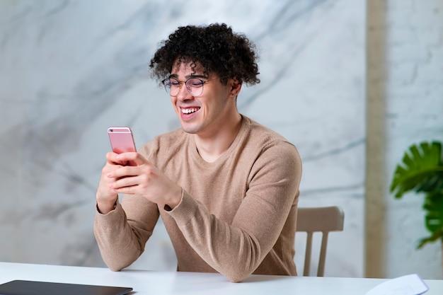 Portret van knappe gelukkig positieve man in glazen, vrolijke jongeman gebruikt gadget, kijken