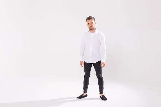 Portret van knappe gelukkige jonge man in casual shirt staande tegen een witte achtergrond met kopie ruimte