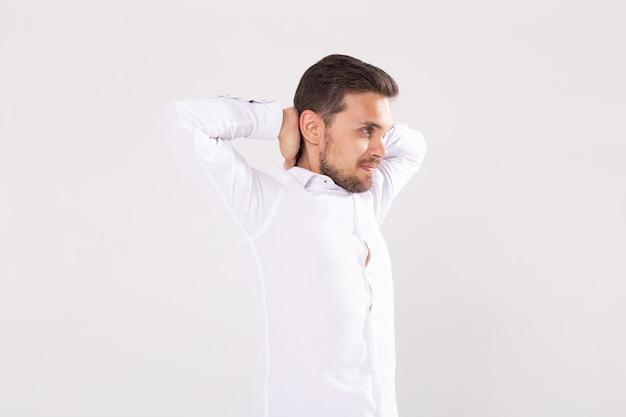 Portret van knappe gelukkige jonge man in casual shirt staande tegen een witte achtergrond.