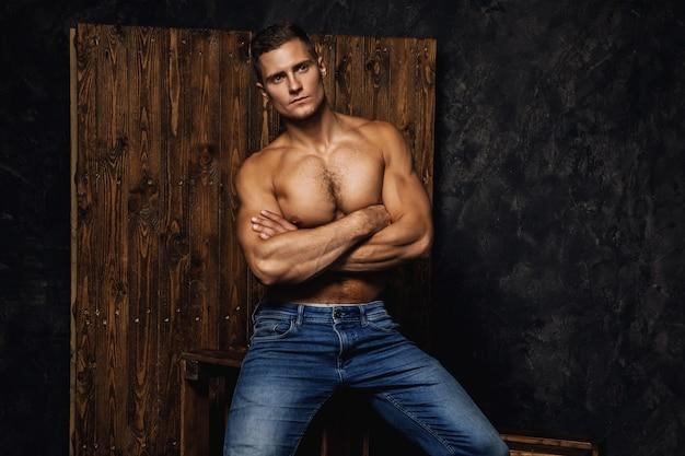 Portret van knappe gespierde en sexy man met spijkerbroek is poseren tegen houten muur