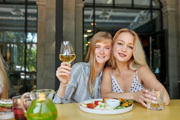 Portret van knappe glimlachende kaukasische vrouwen in restaurant
