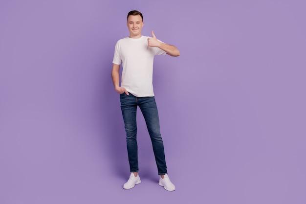 Portret van knappe grappige man duim opdagen op paarse achtergrond