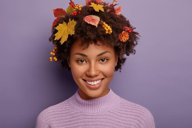Portret van knappe herfst vrouw maakt portret in studio, kijkt vrolijk naar de camera, toont witte tanden, heeft krullend haar met herfstplanten, geïsoleerd tegen paarse studiomuur.