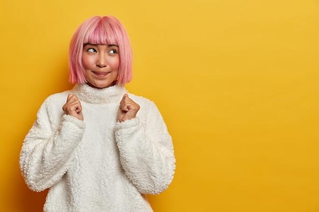 Portret van knappe hoopvolle vrouw met roze kapsel anticipeert op enkele resultaten gebalde vuisten draagt witte warme trui hoopt op positief nieuws dagdromen over overwinning