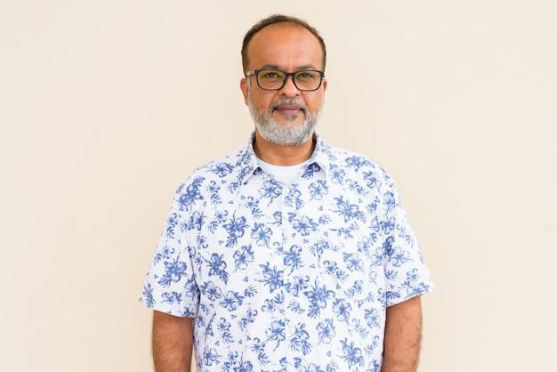 Portret van knappe indiase man met grijze baard tegen effen muur