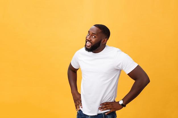 Portret van knappe jonge afrikaanse kerel die in witte t-shirt op gele achtergrond glimlachen
