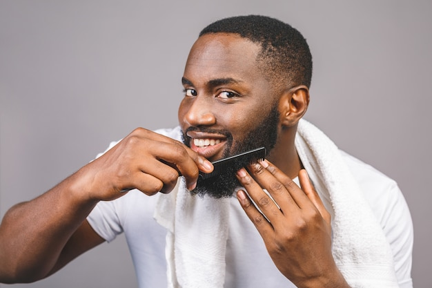 Portret van knappe jonge afro-amerikaanse zwarte man kammen van zijn baard in de badkamer. geïsoleerd over grijze achtergrond.