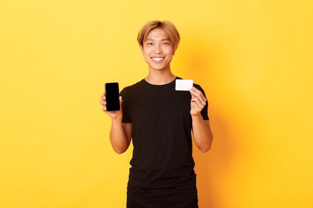 Portret van knappe jonge aziatische kerel die het smartphonescherm, het bankwezen app en creditcard toont, zich gele muur bevindt en glimlacht.