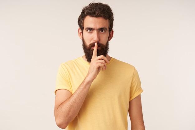 Portret van knappe jonge, bebaarde man met bruine ogen in geel t-shirt met vinger naar mond, kijkend naar je emotie, attente stilte en zelfverzekerd