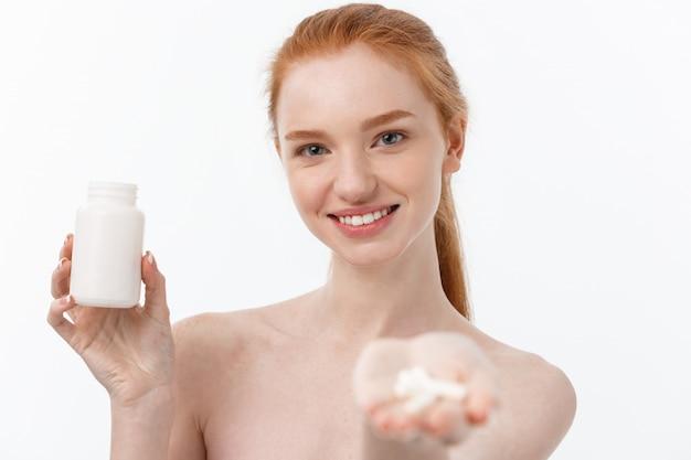 Portret van knappe jonge blanke vrouw met pillen, proberen te zorgen voor immuunsysteem en gezondheid over grijs