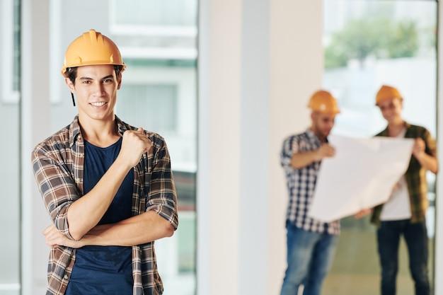 Portret van knappe jonge bouwingenieur met brede glimlach die zich bij bouwwerf bevindt en camera bekijkt