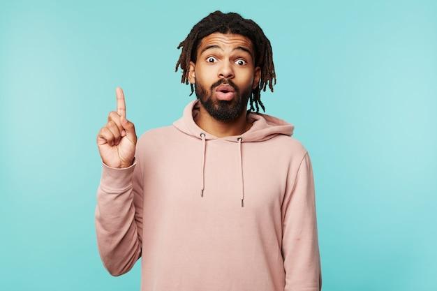 Portret van knappe jonge bruinharige man hand opsteken met idee gebaar en verbaasd kijken naar camera, roze hoodie dragen terwijl poseren op blauwe achtergrond