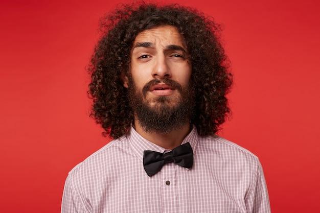 Portret van knappe jonge bruinogige donkerharige krullende man met baard op zoek met opgetrokken wenkbrauw, elegante kleding dragen