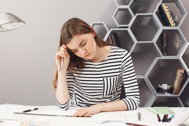 Portret van knappe jonge donkerharige europese freelance meisje in gestreepte shirt tekenen, kijken met ernstige en geconcentreerde gezichtsuitdrukking op papier, op zoek door haar werk.
