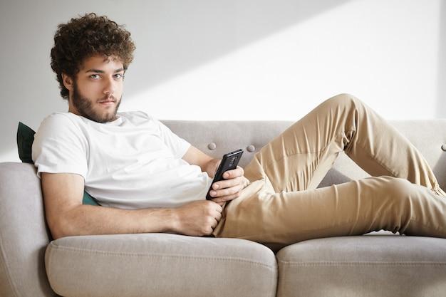Portret van knappe jonge europese man met harig gezicht met rust op comfortabele bank, newsfeed browsen via sociale netwerken op zijn mobiele telefoon, posts liken en reacties online achterlaten