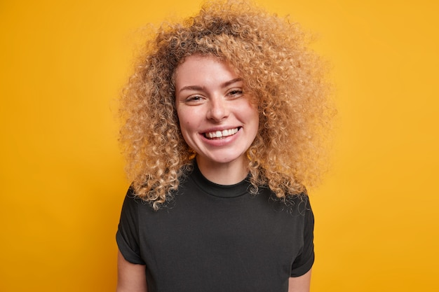 Portret van knappe jonge europese vrouw met krullend borstelig haar gekleed in casual zwart t-shirt glimlacht in grote lijnen positieve emoties geïsoleerd over gele muur lacht met vreugde