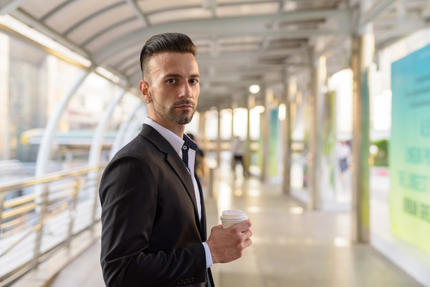 Portret van knappe jonge italiaanse zakenman buiten in stad pak dragen