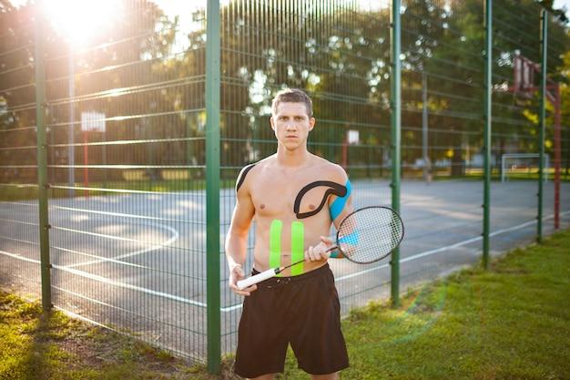 Portret van knappe jonge kaukasische professionele tennisspeler met elastische banden op lichaam dragende racket dichtbij omheind sportveld