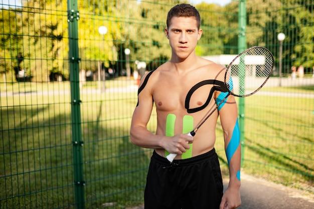 Portret van knappe jonge kaukasische professionele tennisspeler met elastische banden op lichaam dragende racket