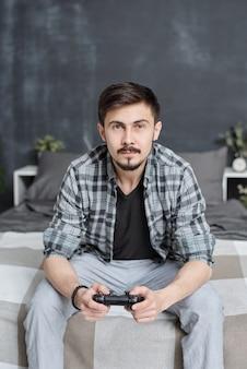 Portret van knappe jonge man in casual shirt zittend op bed en met behulp van joystick tijdens het spelen van videogame thuis
