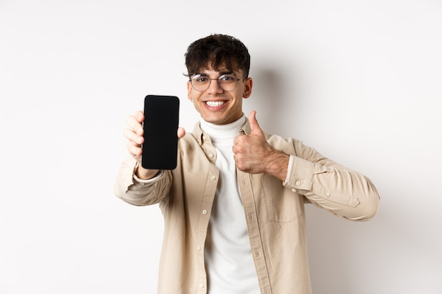 Portret van knappe jonge man in glazen, leeg smartphonescherm en duim tonen, online app of winkel aanbevelen, permanent blij op witte muur.
