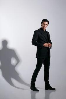 Portret van knappe jonge man in zwart stijlvol pak, geïsoleerd op een witte achtergrond. afbeelding op volledige lengte.