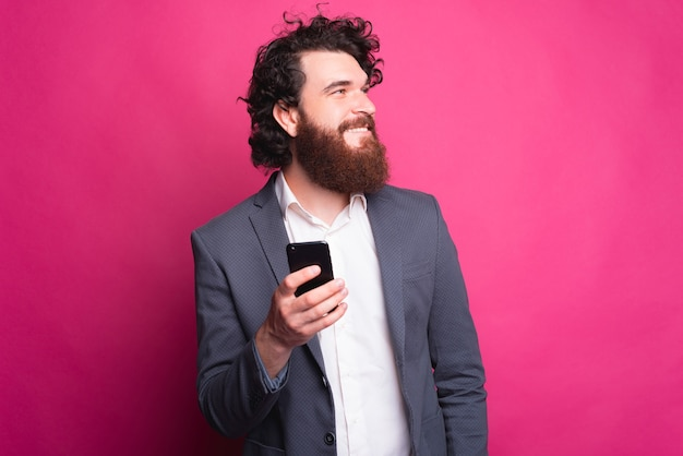 Portret van knappe jonge man met baard is pak slimme telefoon te houden en weg te kijken naar copyspace
