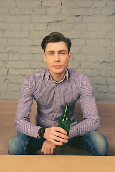 Portret van knappe jonge man met flesje bier en tv kijken