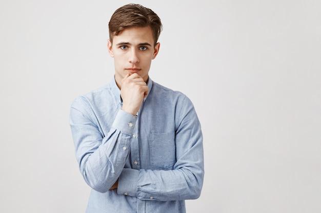 Portret van knappe jonge man met hand op kin, doordachte blik