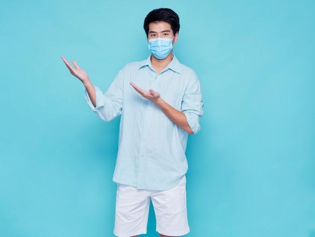 Portret van knappe jonge man met medische masker in casual kleding vinger omhoog. concept covid 19