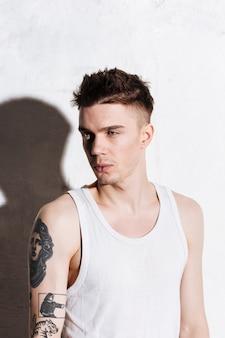 Portret van knappe jonge man met tatoeage op zijn hand