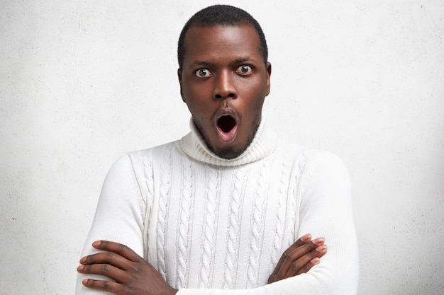 Portret van knappe jonge man met verbaasde uitdrukking, handen gekruist, ziet zijn vijand vooraan, draagt casual witte trui
