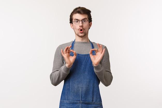 Portret van knappe jonge mannelijke werknemer beveelt geweldige nieuwe koffiesmaak aan, adviseert klant om filter chemex-drank te proberen, oke tekenen te tonen en te garanderen dat je het leuk zult vinden,