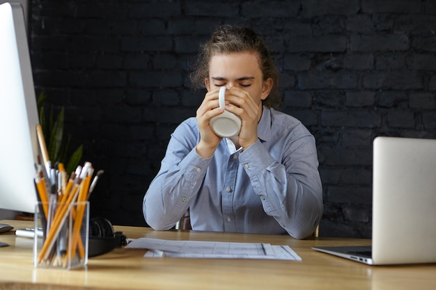 Portret van knappe jonge mannelijke werknemer zittend aan zijn bureau met papieren en moderne elektronische gadgets, mok vasthouden en warme verse koffie of thee drinken terwijl hij zich slaperig of moe voelt