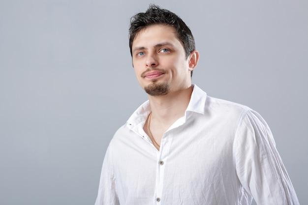 Portret van knappe jonge peinzende brunette man in wit overhemd op grijze achtergrond.