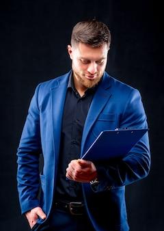 Portret van knappe jonge succesvolle man met donker shirt en blauw pak met blauwe map