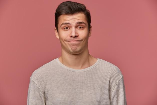 Portret van knappe jonge trieste man draagt in lege t-shirt, kijkt naar de camera met wantrouwen, staat op roze achtergrond.