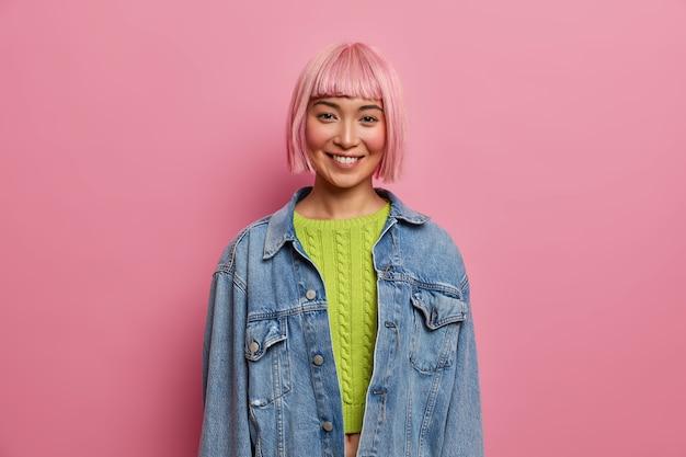 Portret van knappe jonge vrouw met roze kapsel, glimlacht zachtjes, positieve emoties uitdrukt, draagt groene bijgesneden trui, spijkerjasje, vormt binnen. mensen, jeugd, gelukkige gevoelens concept