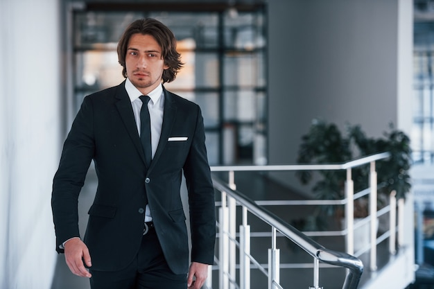 Portret van knappe jonge zakenman in zwart pak en stropdas loopt binnenshuis.